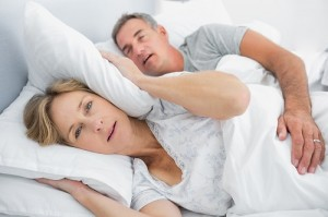 Irritated wife blocking her ears from noise of husband snoring i